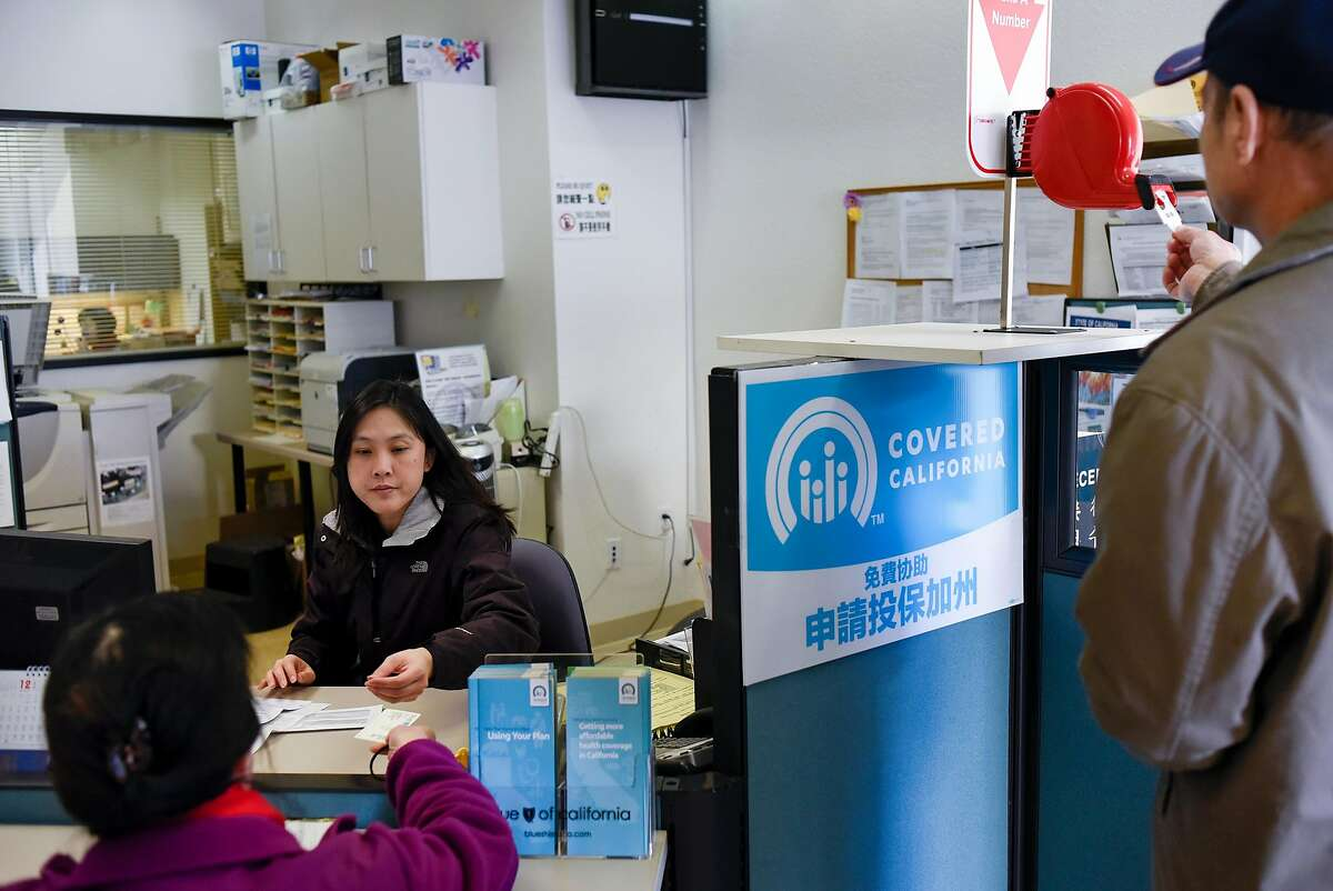 Member services representative Nancy Chen, left, helps customer Zi Yu with her coverage at the Asian Health Services offices in Oakland in 2017. Trump recently slashed the grant program for nonprofit organizations to help consumers buy coverage under the Affordable Care Act.