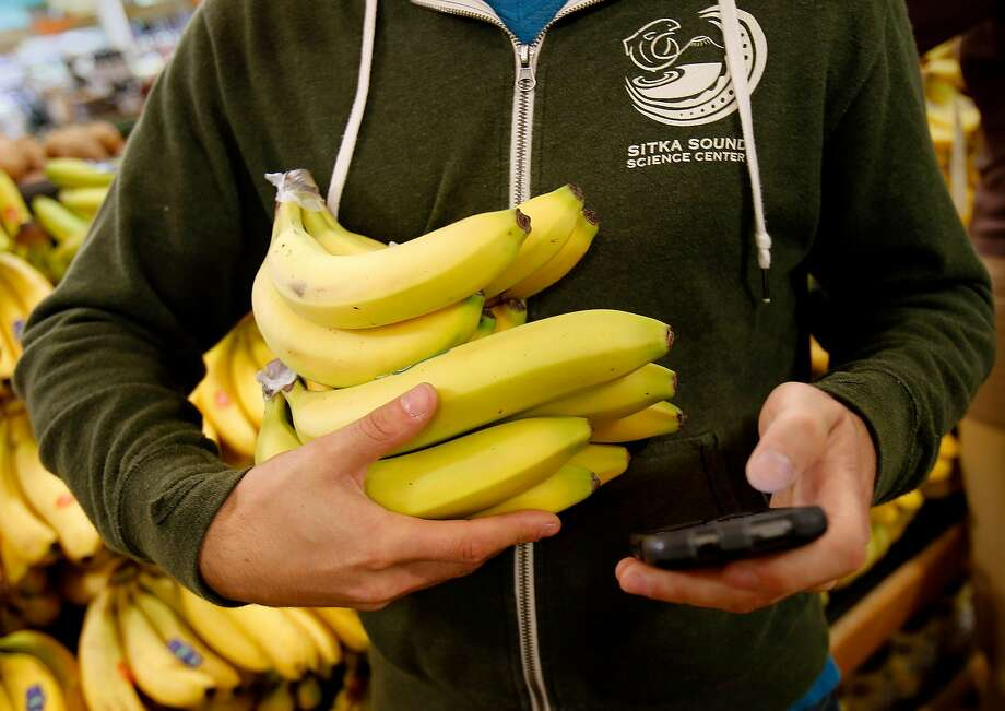 Organic bananas are picked up for an Instacart delivery at Whole Foods Monday November 10, 2014. Yonatan Schkolnik drives paying customers for Sidecar and delivers groceries for Instacart in the Bay Area. Photo: Brant Ward, The Chronicle