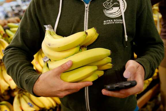 Organic bananas are picked up for an Instacart delivery at Whole Foods Monday November 10, 2014. Yonatan Schkolnik drives paying customers for Sidecar and delivers groceries for Instacart in the Bay Area.