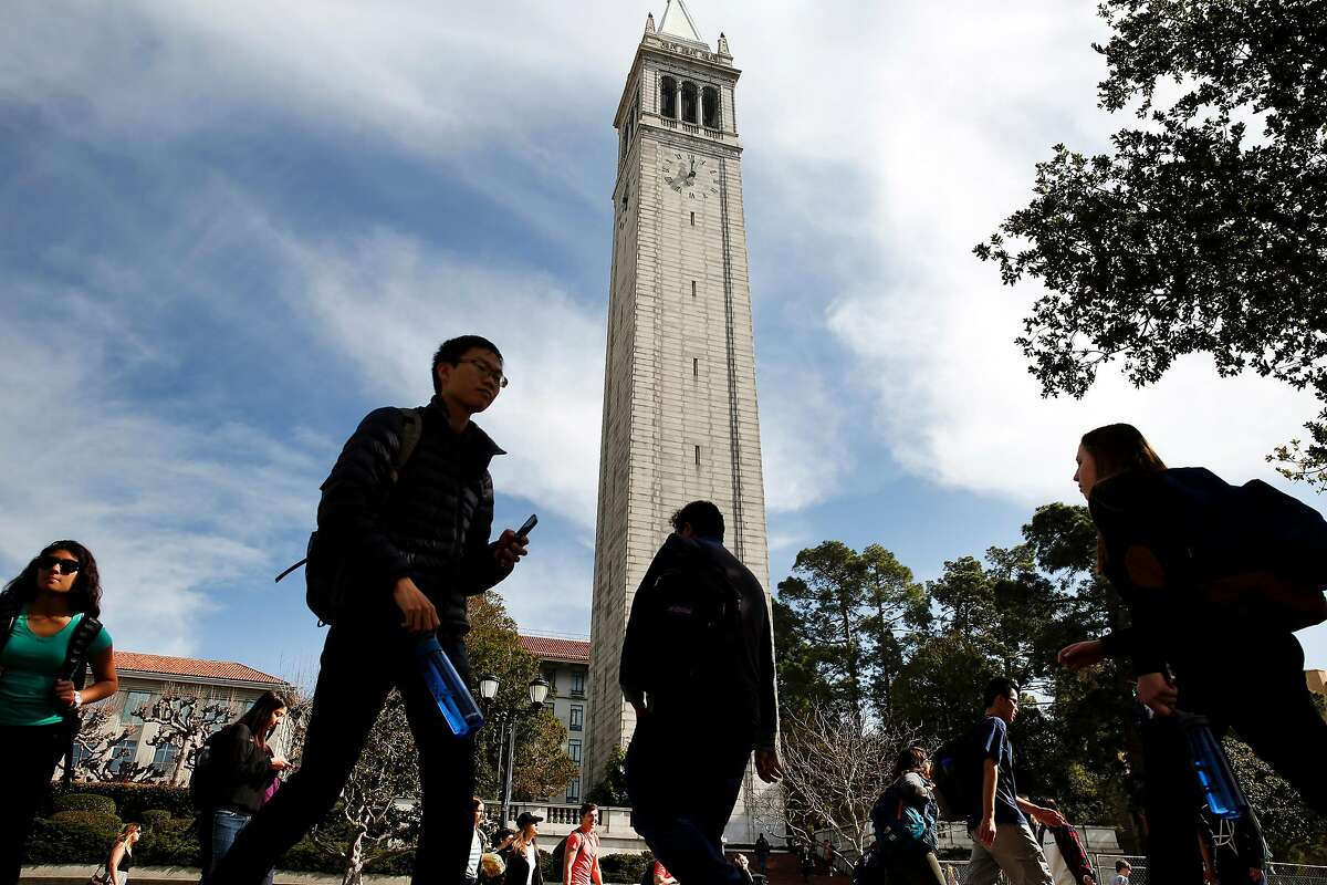 Students pass by the Campanile on the University of California, Berkeley campus.