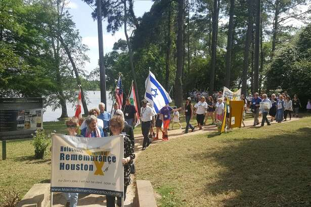People walk along the path of the Holocaust Garden of Remembrance at Kings Harbor in Kingwood during the Holocaust March of Remembrance Saturday, April 22.