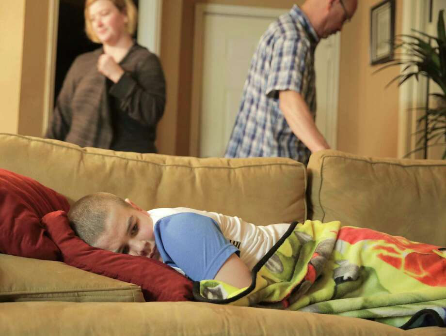 Brayden stays on the sofa as his parents prepare to leave for the hospital. Photo: Elizabeth Conley, Houston Chronicle / © 2017 Houston Chronicle