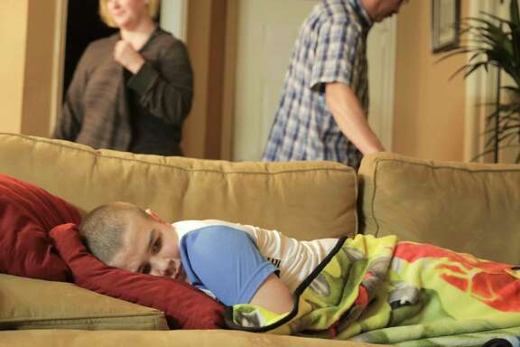 Brayden stays on the sofa as his parents prepare to leave for the hospital.