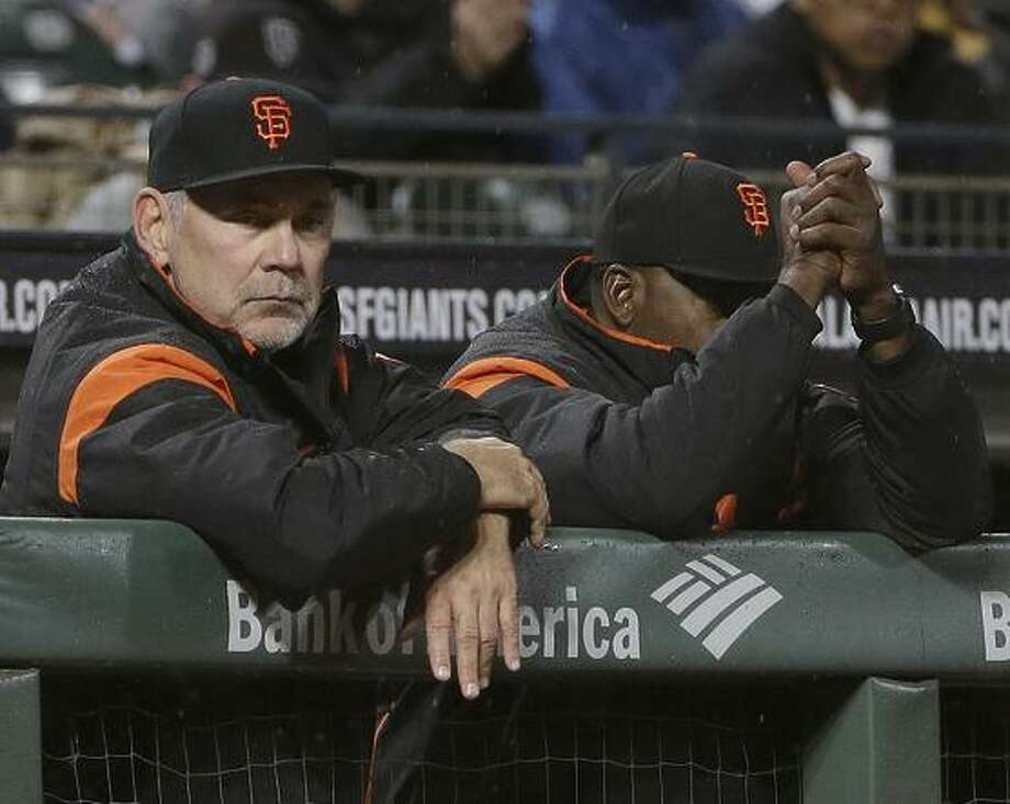 Giants manager Bruce Bochy, left, has had heart procedures in each of the past three years. Buster Posey, right, might have to consider giving up catching. Photo: Jeff Chiu / Associated Press / Copyright 2017 The Associated Press. All rights reserved.