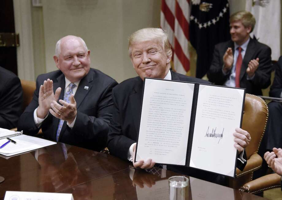 President Donald Trump signs an executive order promoting agriculture and rural prosperity as agriculture secretary Sonny Perdue looks on. Photo: Olivier Douliery, MBR / Abaca Press