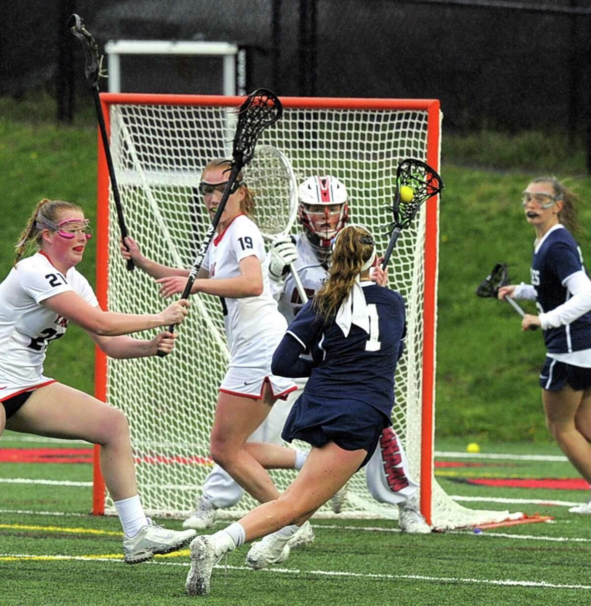 Staples Ellen Fair fires a shot on New Canaan goalie Caroline O'Dea in a varsity girls lacrosse game at New Canaan High School Dunning Field on Tuesday, April 25, 2017. New Canaan defeated Staples 16-8.