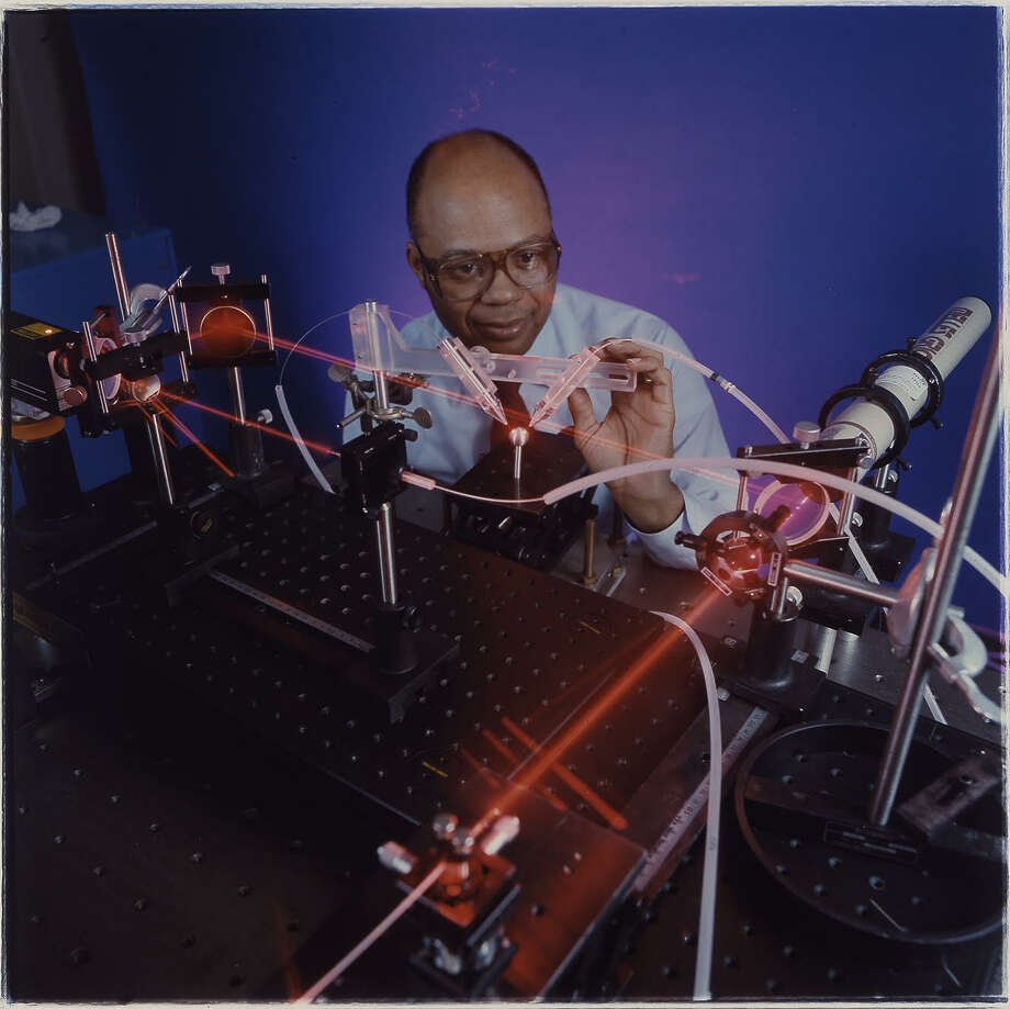Marshall Jones, who holds 55 U.S. patents and is being inducted into the National Inventors Hall of Fame, poses with an industrial laser he used to make innovative breakthroughs in manufacturing. (Photo courtesy of General Electric) Photo: Vae