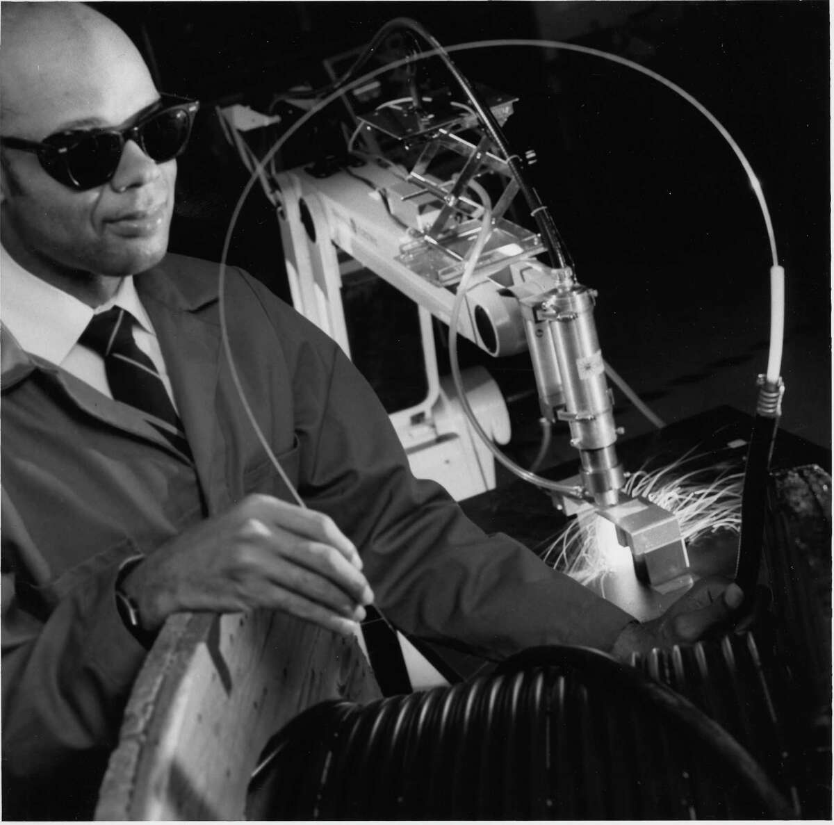 Marshall Jones, who holds 55 U.S. patents and is being inducted into the National Inventors Hall of Fame, poses with an industrial laser he used to make innovative breakthroughs in manufacturing. (Photo courtesy of General Electric)