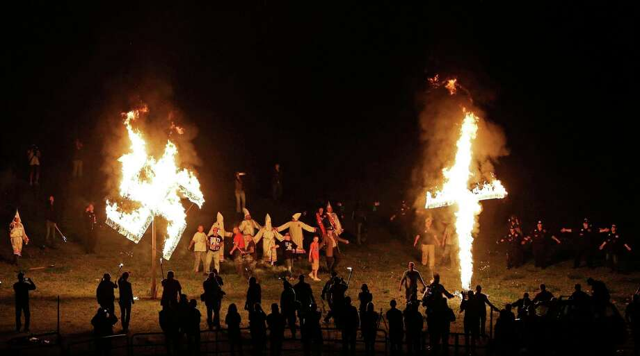 "In 2016, members of the Ku Klux Klan burn a cross and swastika after a ""white pride"" rally in Georgia. The Klan is among groups that have consolidated into the Nationalist Front. Photo: Mike Stewart, STF / Copyright 2016 The Associated Press. All rights reserved. This material may not be published, broadcast, rewritten or redistribu"