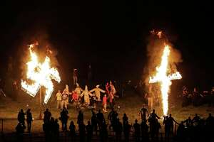 """In 2016, members of the Ku Klux Klan burn a cross and swastika after a """"white pride"""" rally in Georgia. The Klan is among groups that have consolidated into the Nationalist Front."""