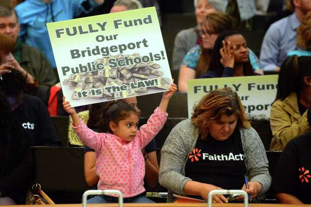 Yarieliz Pagan, 4, holds up a sign demading the city funds the public schools as she and hundreds of parents came out to tell the city council to fully fund the school board budget request during a meeting at City Hall's Council Chambers in Bridgeport, Conn., on Tuesday Apr. 25, 2017. The board wants $11.4 million over what it gets now.