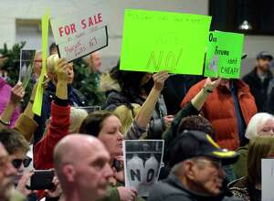 Residents opposed to a revised proposed PFOA settlement hold signs as they try to urge board members to vote no on the proposal during a Village of Hoosick Falls board meeting on Monday, Feb. 27, 2017, in Hoosick Falls, N.Y.  (Paul Buckowski / Times Union)