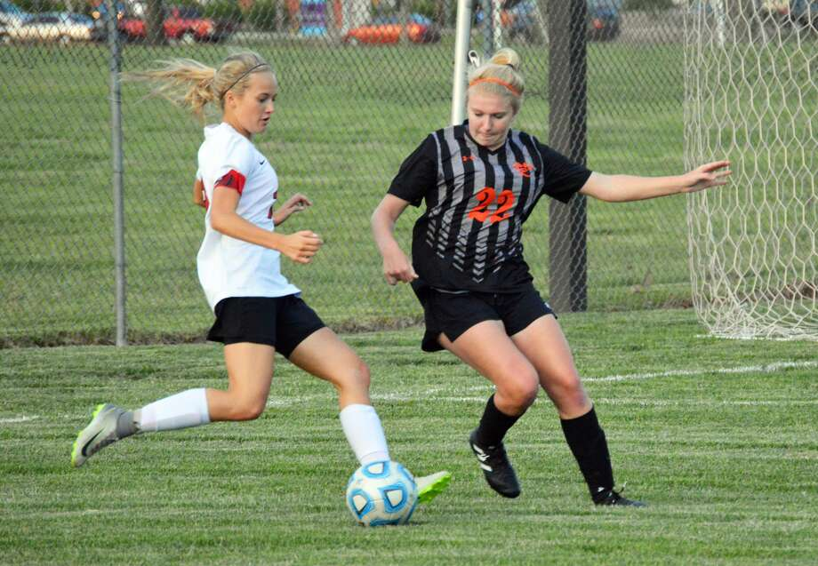 Edwardsville senior defender Taylor Hansen, right, tries to steal the ball late in the first half of Tuesday's game in Granite City.