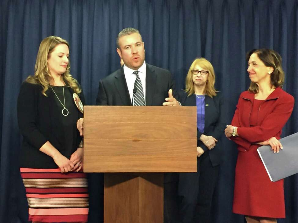 Juan Cruz and his wife, Heather (left), speak in favor of the Child-Parent Security Act at a press conference in Albany, N.Y., Tuesday, April 25, 2017. The legislation would overhaul state laws restricting gestational surrogacy to allow for contractual surrogacy agreements and payment for a gestational carrier.