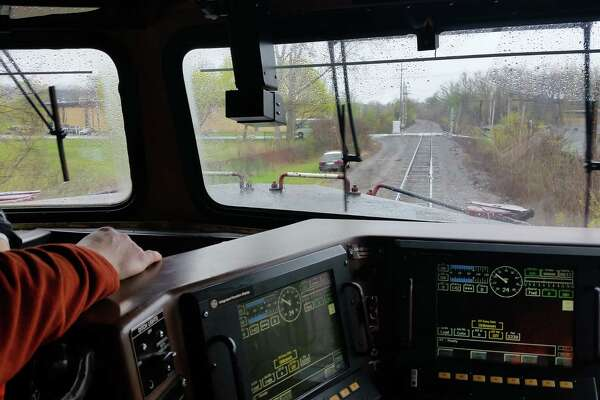 Canadian Pacific railroad enigineer Eric Brindle looks out from his cab at an upcoming rail crossing