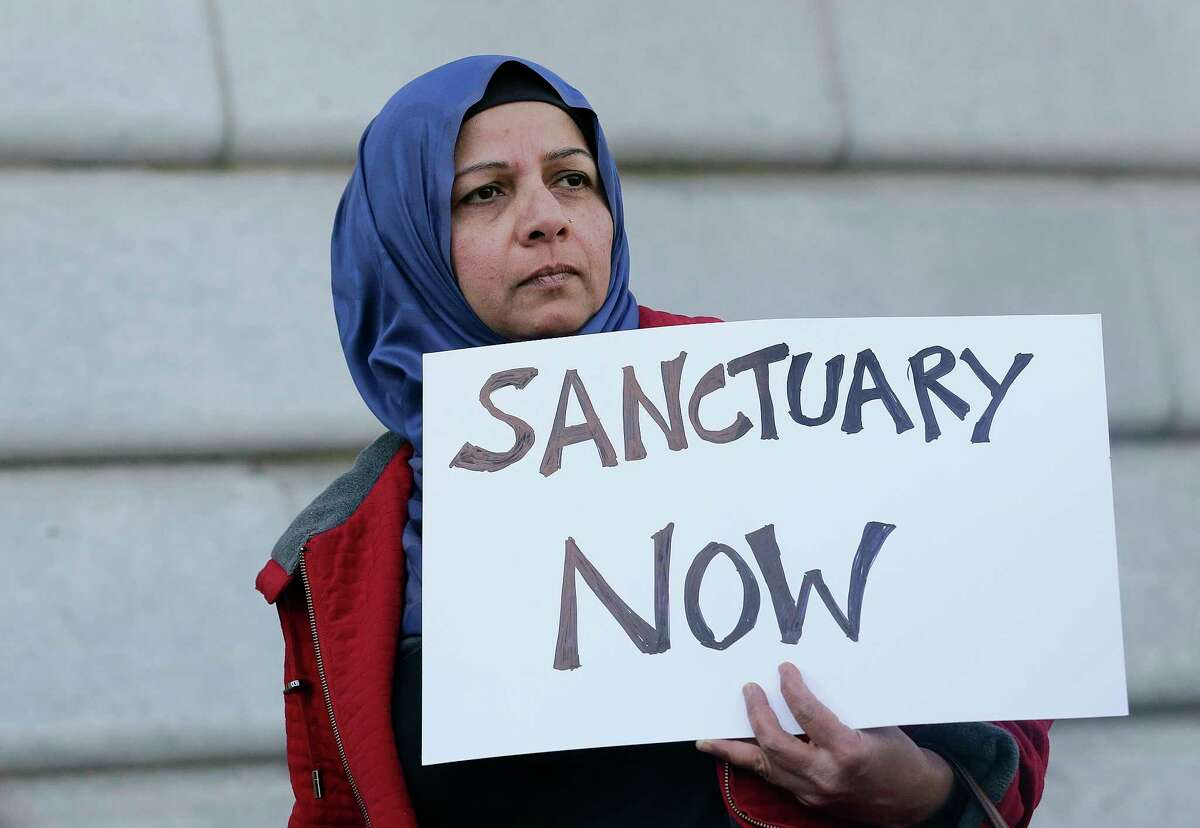 FILE - In this Jan. 25, 2017 file photo, Moina Shaiq holds a sign at a rally outside of City Hall in San Francisco. On Tuesday, April 25, 2017, a federal judge blocked a Trump administration order to withhold funding from communities that limit cooperation with U.S. immigration authorities, saying the president has no authority to attach new conditions to federal spending. (AP Photo/Jeff Chiu, File) ORG XMIT: FX102