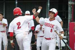 Clear Brook's Reggie McCalister (2) and Clear Brook's Jerick Paquinto (8) celebrate a run scored against Dickinson Tuesday, Apr. 25 at Clear Brook High School.