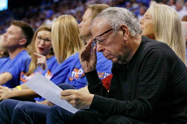 Leslie Alexander, owner of the Houston Rockets, looks over a stat sheet during the third quarter of the team's first-round NBA basketball playoff game against the Oklahoma City Thunder in Oklahoma City, Friday, April 21, 2017. Oklahoma City won 115-113. (AP Photo/Sue Ogrocki)