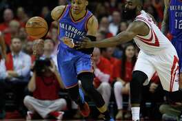 Houston Rockets guard James Harden (13) fights Oklahoma City Thunder guard Russell Westbrook (0) for a loose ball in the second half of Game 5 of a Western Conference quarterfinals of the 2017 NBA playoffs, April 24, 2017, in Houston.