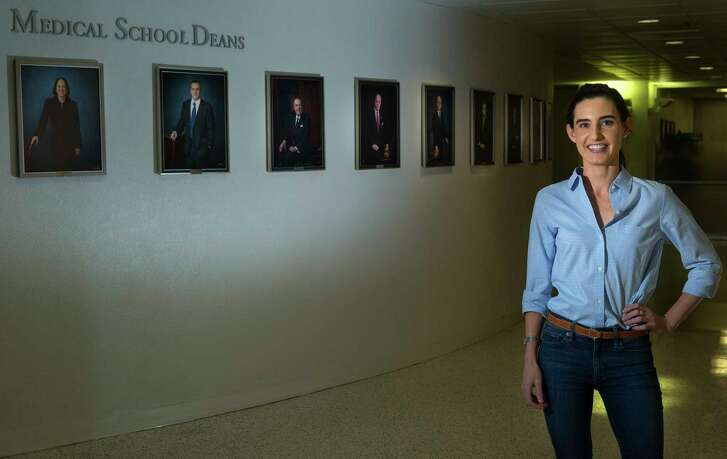 Caroline Hussey, a second-year medical student at UTHealth, recently learned about the huge wage disparity between men and women doctors that can exist. Hussey is standing in front of a wall showing pictures of the McGovern school's deans, who until the most recent dean, were all men, Tuesday, April 24, 2017, in Houston. (Mark Mulligan / Houston Chronicle)