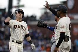 San Francisco Giants' Christian Arroyo, left, points skyward after hitting a single during the first inning of the team's baseball game against the Los Angeles Dodgers on Tuesday, April 25, 2017, in San Francisco. (AP Photo/Marcio Jose Sanchez)