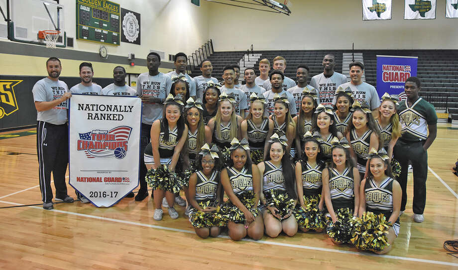 The Cy Falls Golden Eagles pose alongside the coaches and cheerleaders, following the presentation of the MaxPreps Tour of Champions Minuteman Award Tuesday at Cy Falls High School. MaxPreps declared Cy Falls the 17th-best team in the country, out of a pool of more than 40,000 high school programs. Photo: CFISD Communications