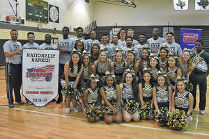 The Cy Falls Golden Eagles pose alongside the coaches and cheerleaders, following the presentation of the MaxPreps Tour of Champions Minuteman Award Tuesday at Cy Falls High School. MaxPreps declared Cy Falls the 17th-best team in the country, out of a pool of more than 40,000 high school programs.