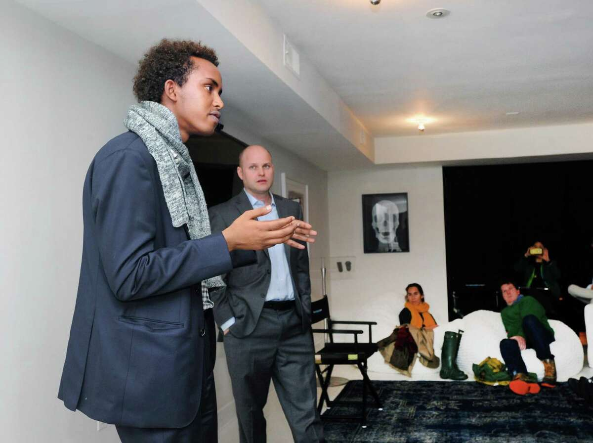 """Jonathan Starr, founder of the Abaarso School of Science and Technology in Somaliland, listened as his former student, now a Brown University student, Abdirahim Mohamed, left, spoke about his native Somaliland during the event """"It takes a school: an American school in Somaliland,"""" at the Nantucket Project in Greenwich, Conn., Tuesday night, April 25, 2017."""