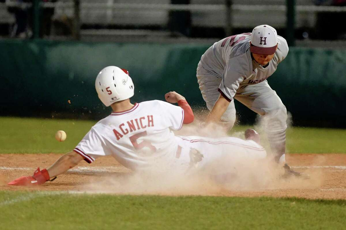 Dylan Angich scores when the ball gets away from the Heights catcher in the fourth inning of a varsity baseball game between the Bellaire Cardinals and the Heights Bulldogs on Tuesday April 25, 2017 at Knoblauch Field, Houston, TX.