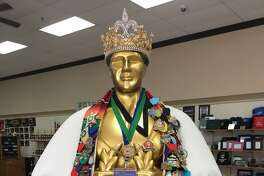 The regal robe and jewel-encrusted crown of El Rey Feo LXIII Bill Drain is on display at Monarch Trophy, bedecked by medals made by Monarch.