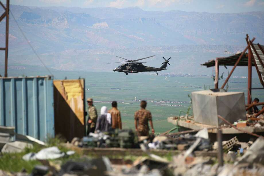 "TOPSHOT - A medical helicopter, from the US-led coalition, flies over the site of Turkish airstrikes near northeastern Syrian Kurdish town of Derik, known as al-Malikiyah in Arabic, on April 25, 2017. Turkish warplanes killed more than 20 Kurdish fighters in strikes in Syria and Iraq, where the Kurds are key players in the battle against the Islamic State group. The bombardment near the city of Al-Malikiyah in northeastern Syria saw Turkish planes carry out ""dozens of simultaneous air strikes"" on YPG positions overnight, including a media centre, the Syrian Observatory for Human Rights said. / AFP PHOTO / DELIL SOULEIMANDELIL SOULEIMAN/AFP/Getty Images Photo: DELIL SOULEIMAN, Stringer / AFP/Getty Images / AFP or licensors"