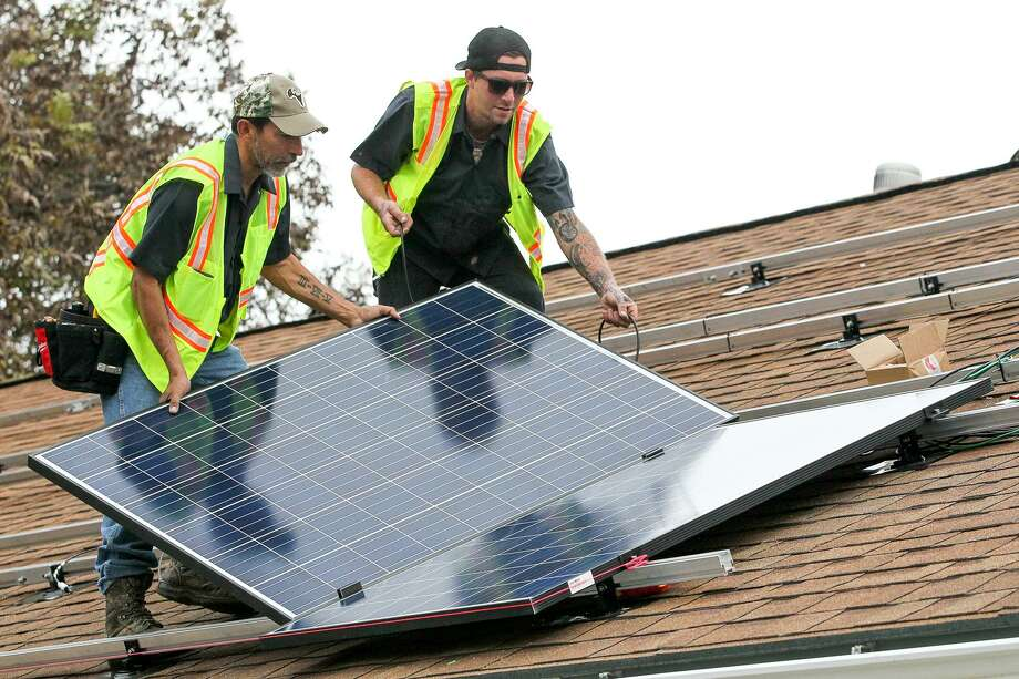 Solar installers place panels on a roof in San Antonio. CPS Energy and local solar companies met Wednesday to discuss new rules that could come into effect as early as June 1. Photo: Marvin Pfeiffer /San Antonio Express-News / Express-News 2015