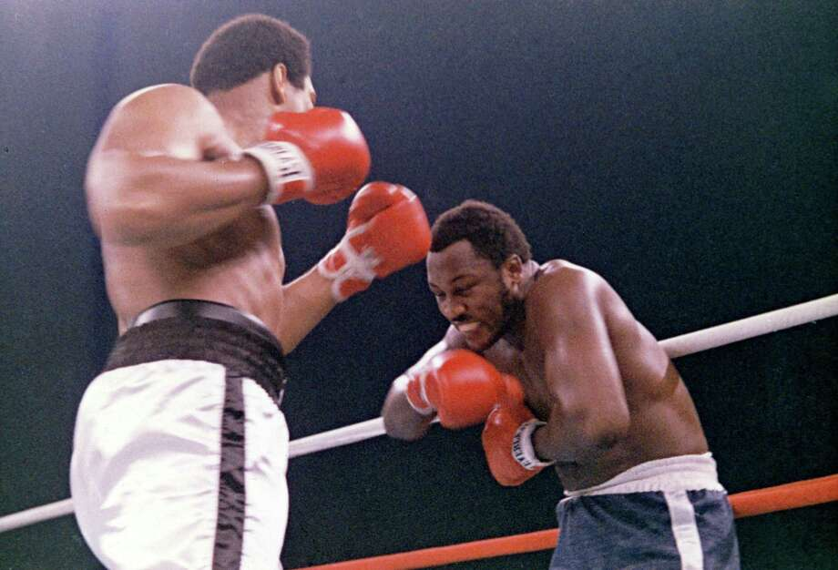 """In this Oct. 1, 1975, file photo, heavyweight boxer Joe Frazier grimaces after Muhammad Ali, left, landed a blow to Frazier's head during their boxing bout in Manila, the Philippines. One Stratford town councilman has likened an upcoming session between the council and Board of Education as the """"Thrilla in Manila.""""(AP Photo/File) Photo: / AP / 1975 AP"""