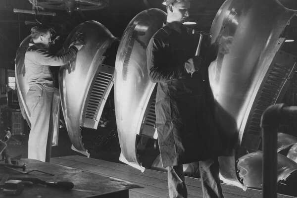 Workers inspecting fenders before painting at a factory, USA, circa 1930. The fender is the pressed and formed sheet-metal part mounted over the wheels of an automobile to reduce the splashing of mud and water (Photo by Archive Photos/Getty Images)