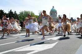 "Serbian women take part in a wedding dress race in downtown Belgrade on June 19, 2011. More than fifty ""brides"" took part in an annual wedding dress race in the Serbian capital, competing for numerous prizes.   AFP PHOTO / ANDREJ ISAKOVIC (Photo credit should read ANDREJ ISAKOVIC/AFP/Getty Images)"