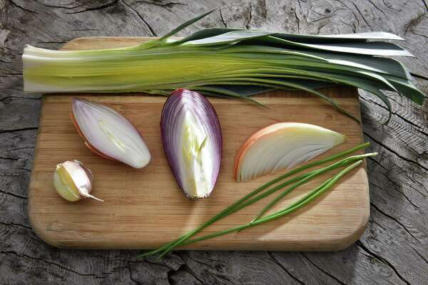 Ingredients for this installment of Caroline Barrett's Bold Flavors, a leek, at top, and from left garlic, shallot, red onion, yellow onion and chive Thursday April 20, 2017 in Delmar, NY.  (John Carl D'Annibale / Times Union)