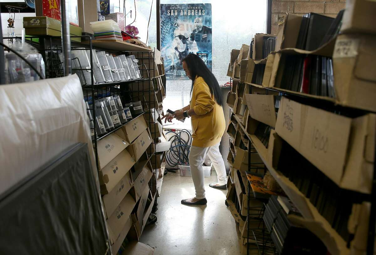 Owner Sheila Burch of Nickelodeon Entertainment looks for media bought by customers as she tries to clear her store on Tuesday, April 25, 2017, in Pacifica, Calif. Her thirty three year old video store is closing this coming Sunday.