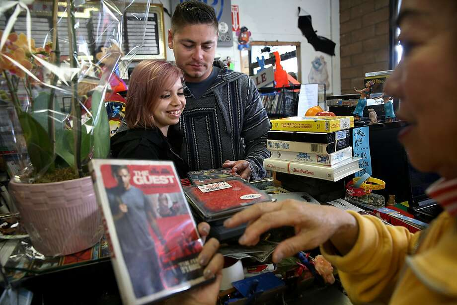 Owner Sheila Burch (right) of Nickelodeon Entertainment looks at dvd's picked by the girlfriend Stephanie Guitar of longtime customer Reuben Gonzalez (middle) from Pacifica on Tuesday, April 25, 2017, in Pacifica, Calif. Photo: Liz Hafalia, The Chronicle