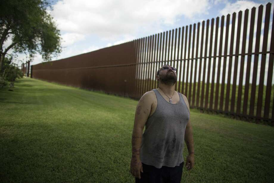 Antonio Reyes of Brownsville, Texas, stands by the U.S.-Mexico border fence near his home on March 22. Reyes said he's seen people scale the border fence that bisects his backyard and jump down in seconds. Photo: Rodrigo Abd /Associated Press / Copyright 2017 The Associated Press. All rights reserved.