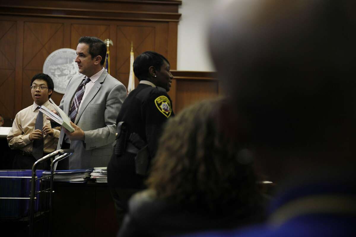 Brendan Loftus (second from left), paralegal with public defender's office, calls out the name of people scheduled to appear in the Community Justice Center courtroom on Monday, March 3, 2014, in San Francisco, Calif.