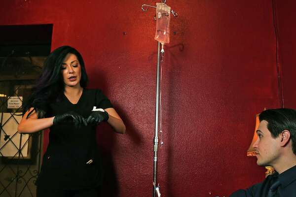 Jackie Bowers, left, owner of Alamo IV, prepares to give an intravenous infusion of electrolytes and vitamin B to Jordan Corney, bar manager at Bohanan's Prime Steak and Seafood. Corney said the IV helps him survive the long hours during Fiesta.