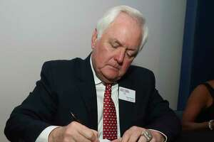 Wade Phillips autographs a poster of his coaching days in the NFL with the Denver Broncos Tuesday Feb. 21, 2017, in Waco, Texas before being inducted into the Texas Sports Hall of Fame class of 2017. (Jerry Larson/Waco Tribune Herald via AP)