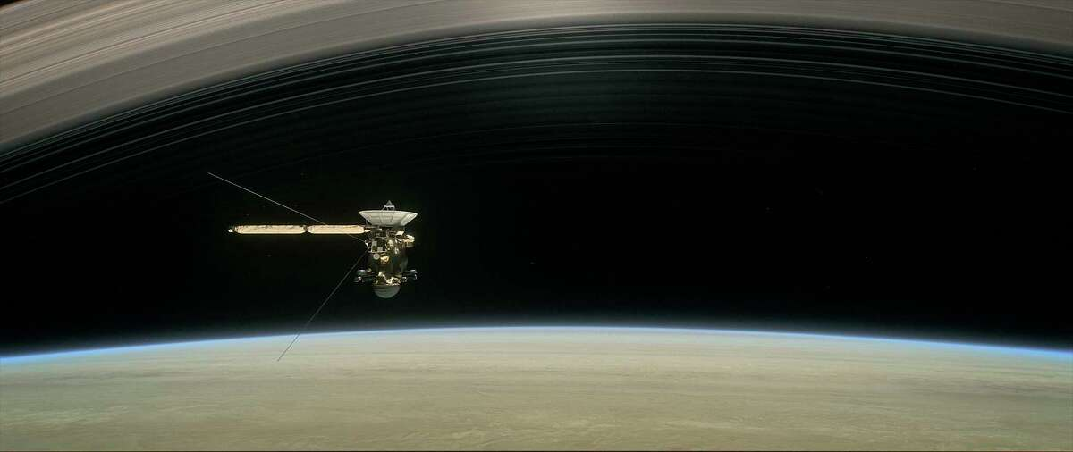 """This image shows a still from the short film """"Cassini's Grand Finale,"""" with the spacecraft diving between Saturn and its innermost ring. Launched in 1997, Cassini reached Saturn in 2004."""