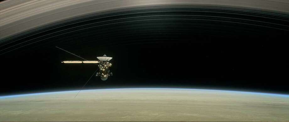 "This image shows a still from the short film ""Cassini's Grand Finale,"" with the spacecraft diving between Saturn and its innermost ring. Launched in 1997, Cassini reached Saturn in 2004. Photo: HOGP / NASA/JPL-Caltech"
