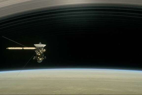 "This image shows a still from the short film ""Cassini's Grand Finale,"" with the spacecraft diving between Saturn and its innermost ring. Launched in 1997, Cassini reached Saturn in 2004."
