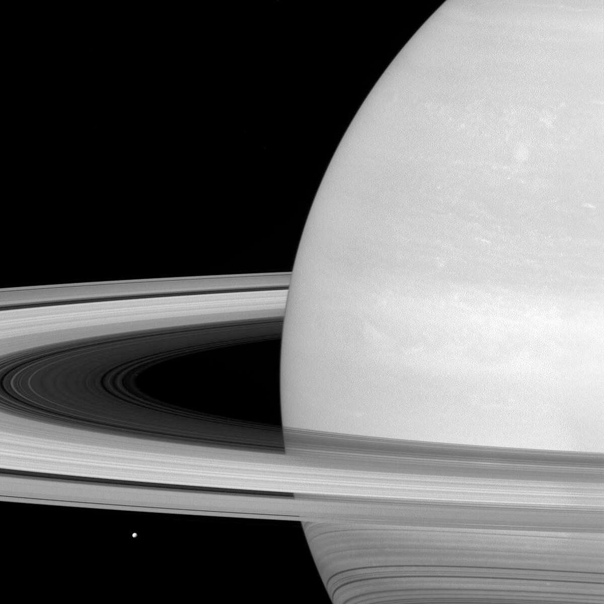 This undated photo made available by NASA shows one of Saturn's moons, Mimas, dwarfed by the planet's rings. Launched in 1997, Cassini reached Saturn in 2004 and has been exploring it from orbit ever since. CassiniÂ?'s fuel tank is almost empty, so NASA has opted for a risky, but science-rich grand finale. (NASA/JPL-Caltech/Space Science Institute via AP)