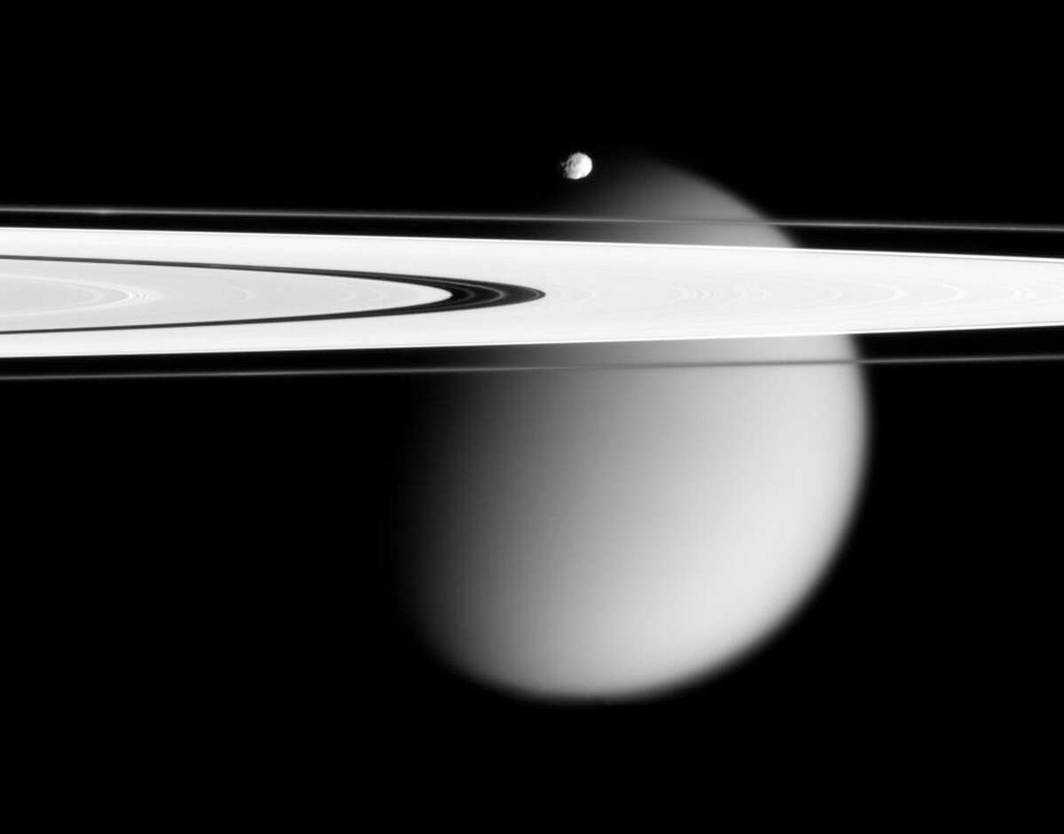 This image made by the Cassini spacecraft and provided by NASA on March 12, 2006, shows two of Saturn's moons, the small Epimetheus and smog-enshrouded Titan, with Saturn's A and F rings stretching across the frame. Launched in 1997, Cassini reached Saturn in 2004 and has been exploring it from orbit ever since. CassiniÂ?'s fuel tank is almost empty, so NASA has opted for a risky, but science-rich grand finale. (AP Photo/NASA)