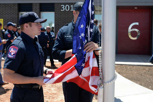 Midland firefighters from left, Dusty Schauer and Clay Perkins hold the US flag during the grand opening ceremony for Fire Station 6 on April 26, 2017. James Durbin/Reporter-Telegram