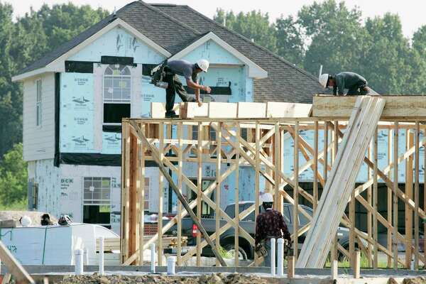 Construction workers build a new home in Houston. (AP Photo/David J. Phillip)