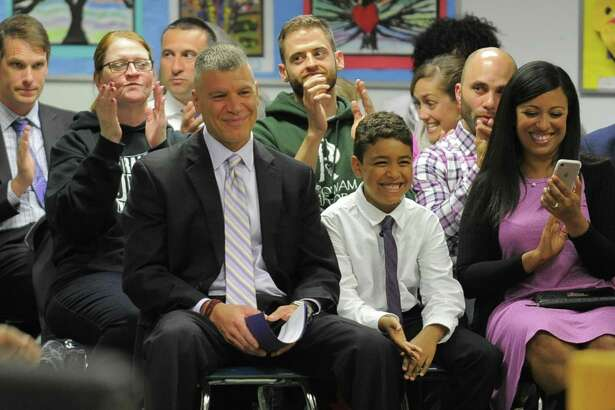 Michael Rinaldi smiles as members of the Stamford Board of Education unanimously approved his appointment as new principal for Westhill High School on Tuesday, April 25, 2017 during the Stamford Board of Education meeting. Rinaldi, a Stamford native and graduate of Westhill High School, will replace outgoing principal Camille Figluizzi, who is retiring. At right is his son Nikolas and wife Jennifer.